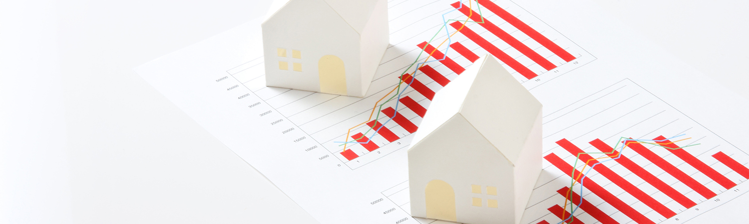 White Model Houses Placed on a Printout of Charts