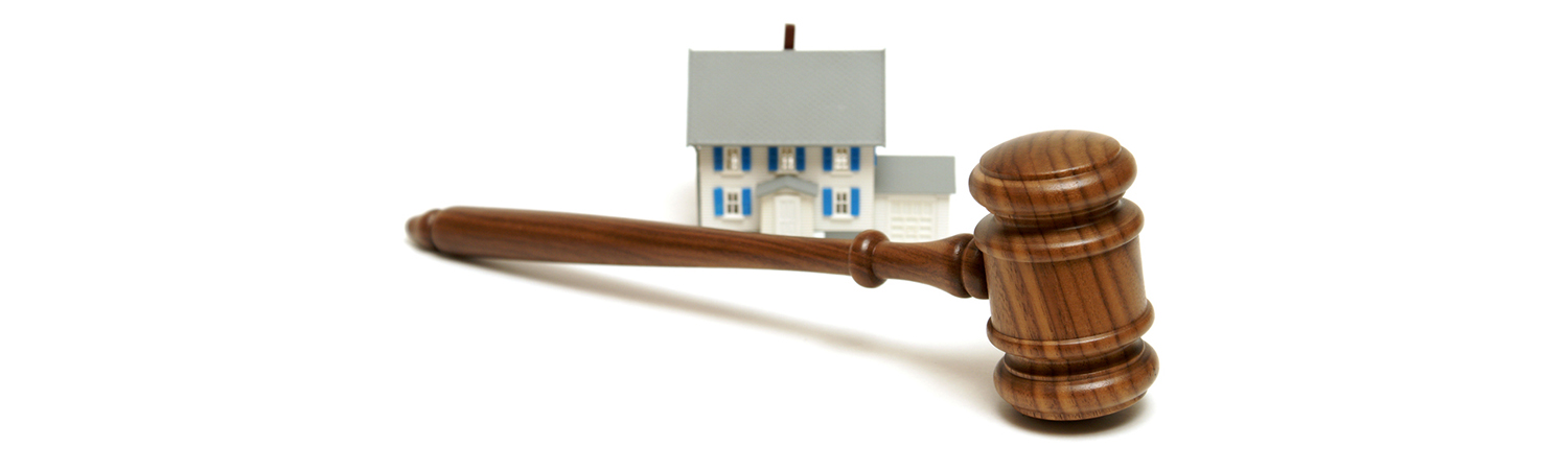 Gavel Foreground with Model House in Background